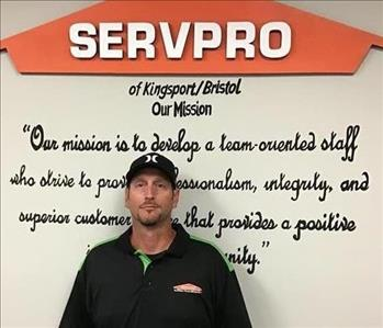 Male employee in front of mission statement on wall